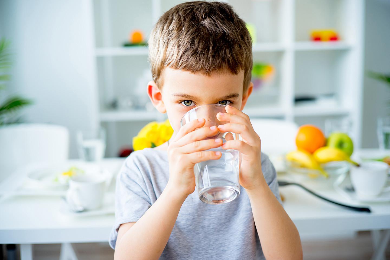 Dziecko pije przefiltrowaną wodę