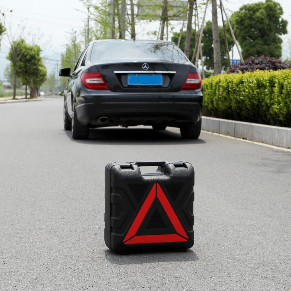 Walizka z trójkątem ostrzegawczym ustawiona kawałek od samochodu