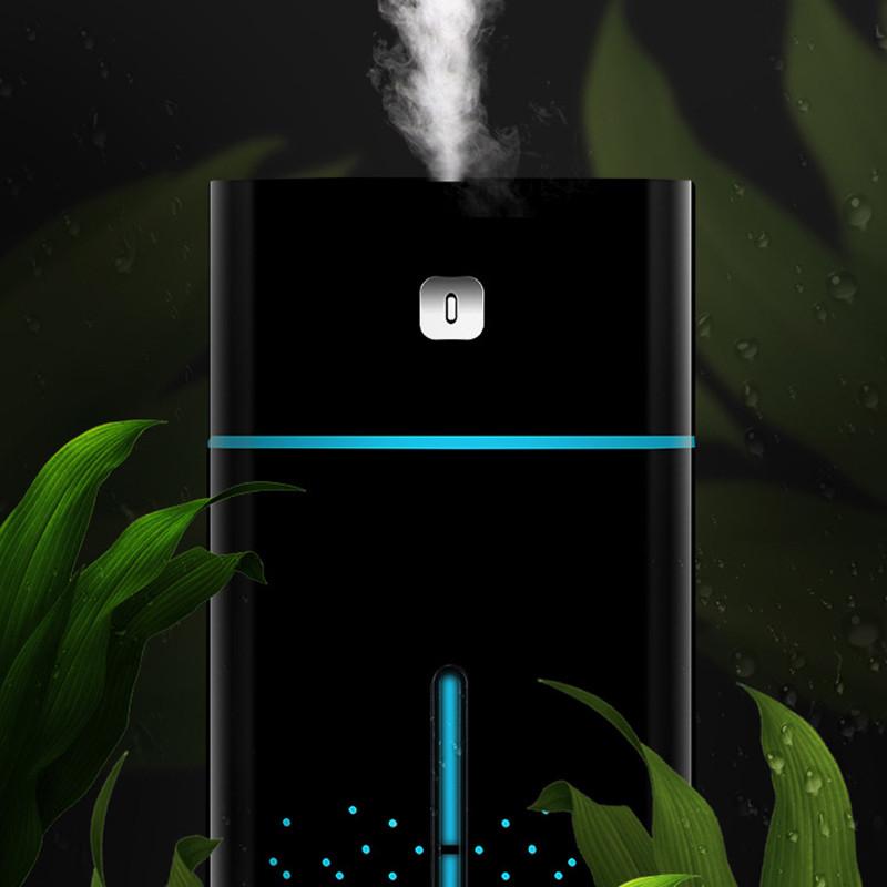 Czarny nawilżacz powietrza na tle zielonych liści
