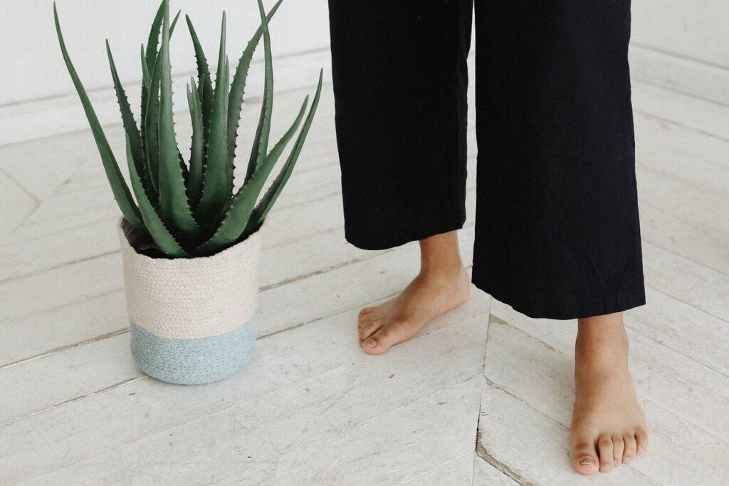 Maty grzewcze na podczerwień pod podłogą w salonie, na które stoi osoba bez butów