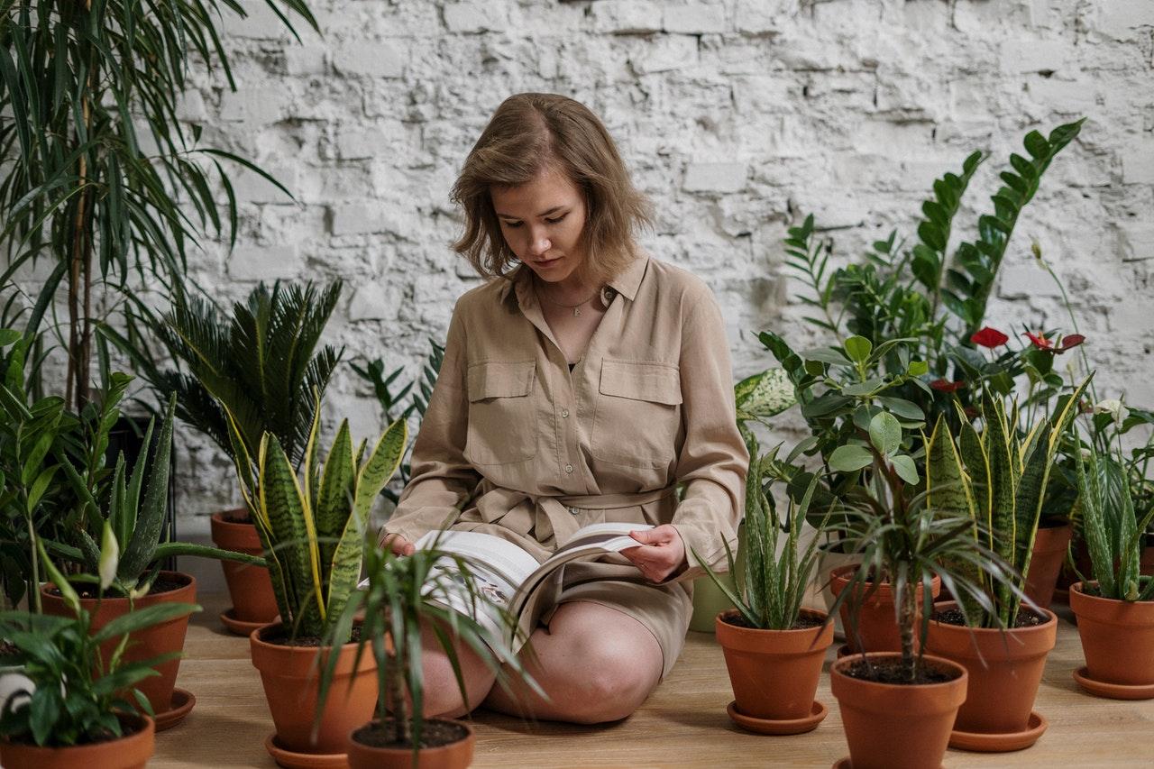 Kobieta czyta książkę Uprawa roślin w otoczeniu kwiatów