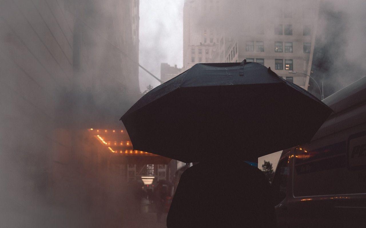 Zanieczyszczenie powietrza w mieście w postaci oparów i idąca przez nie osoba